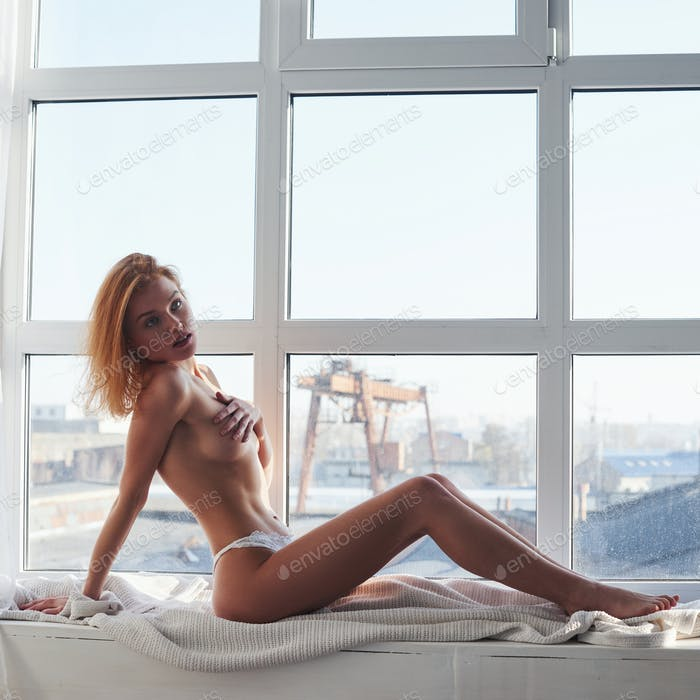 Almost naked redhead girl lying on the windowsill and covering her bare chest by the hand