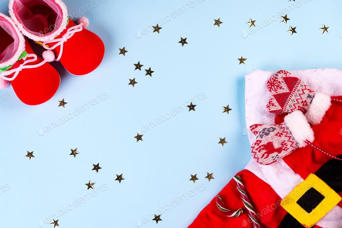 santa claus clothes with shoes and mittens on a blue background, stars on the background, top view