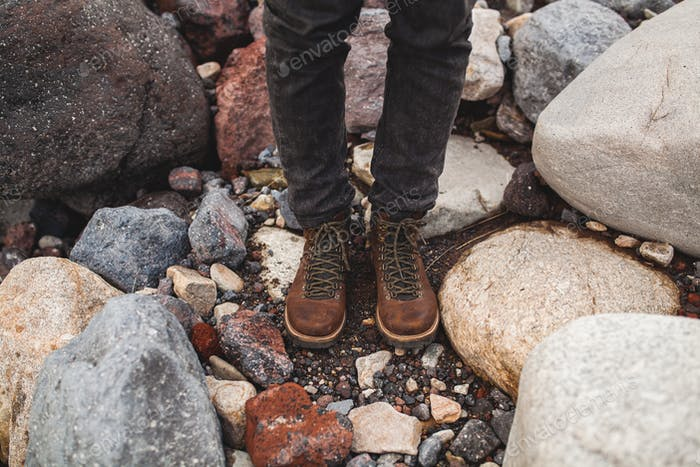 legs in shoes of young hipster man hiking in mountains