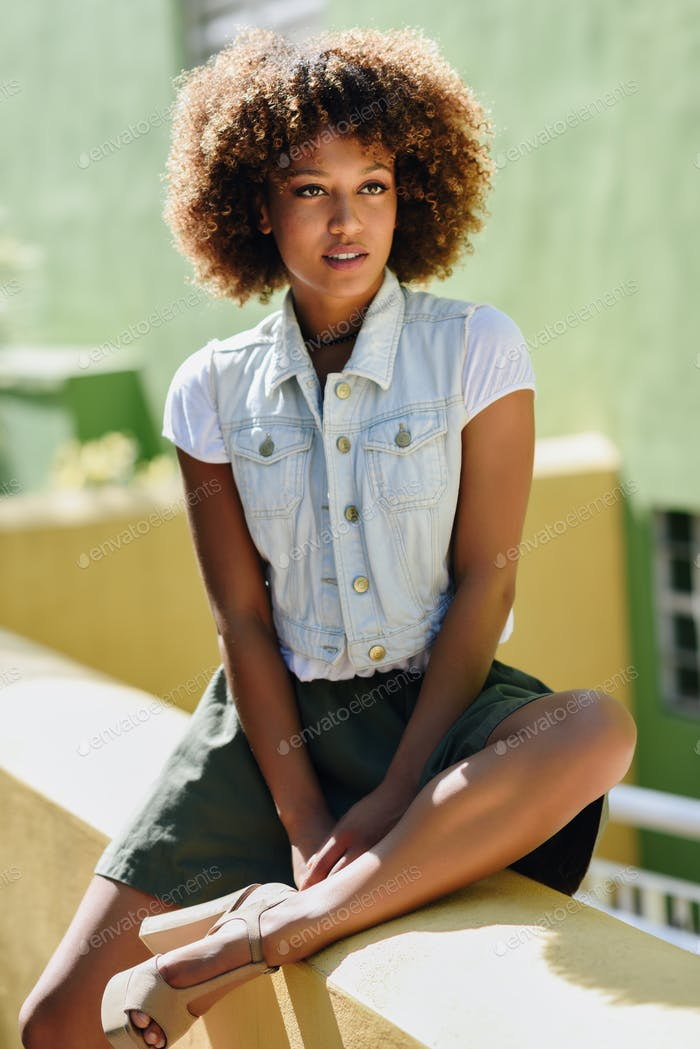 Black woman, afro hairstyle, wearing casual clothes in urban bac