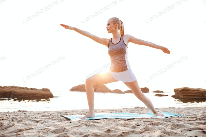 Concentrated young woman standing in yoga pose outdoors