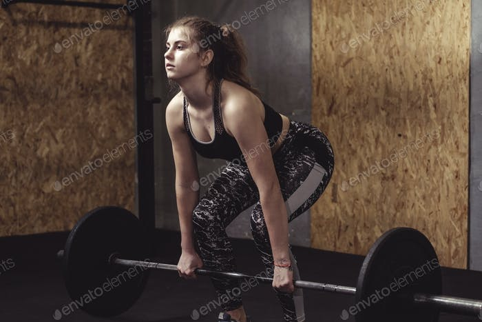 Young woman training lifting weights