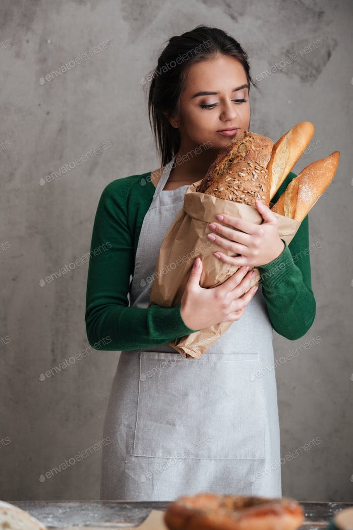 Young happy lady baker standing and holding bread.