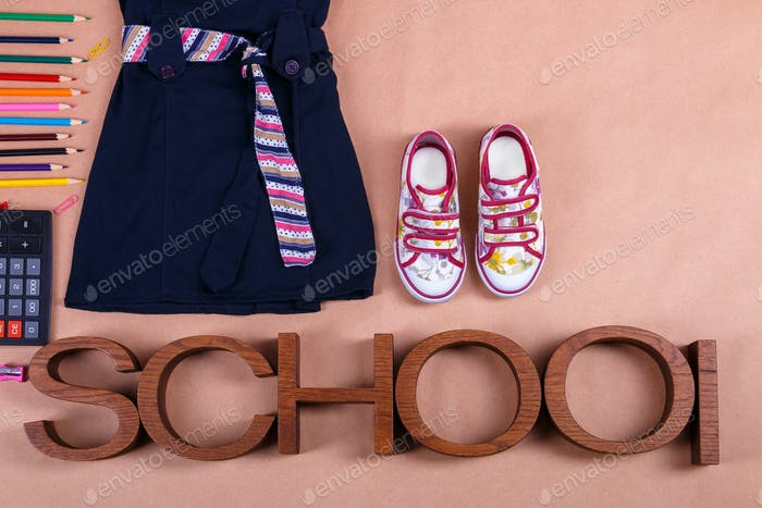 School uniform near sneakers and  supplies on orange