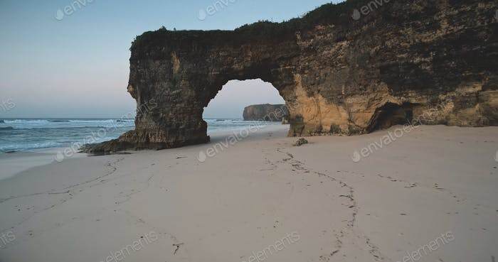 Unique geological formation of Batu Bolong - giant hole in rock wall at sand beach, ocean bay aerial