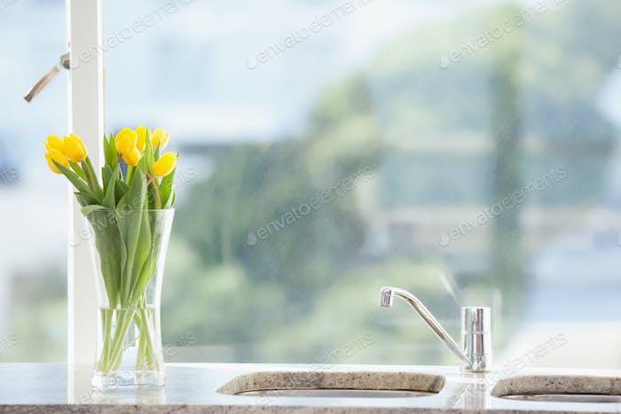 Gelbe Blume in einer Vase auf der Spüle zu Hause im Wohnzimmer