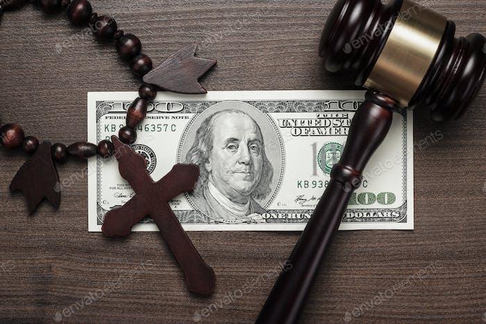 Holzkreuz Gavel und Geld auf braunem Tisch Hintergrund