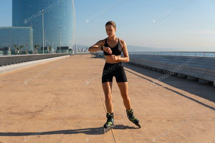 Sportswoman on roller skates checking pulse