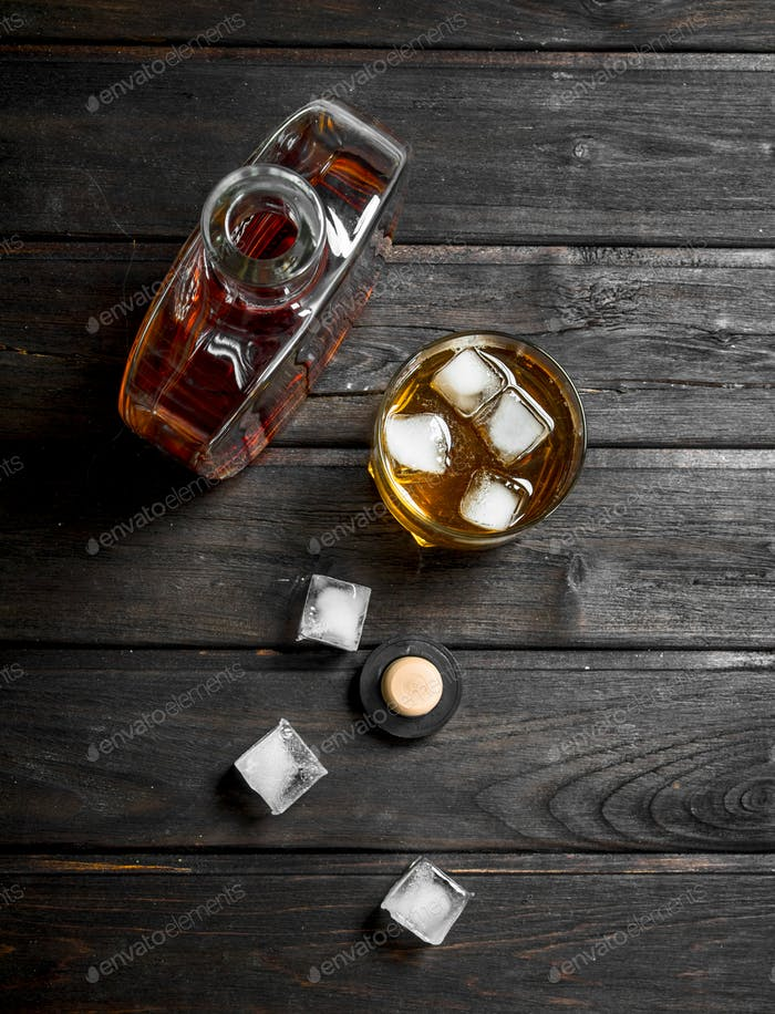 Whiskey in a bottle with ice cubes.