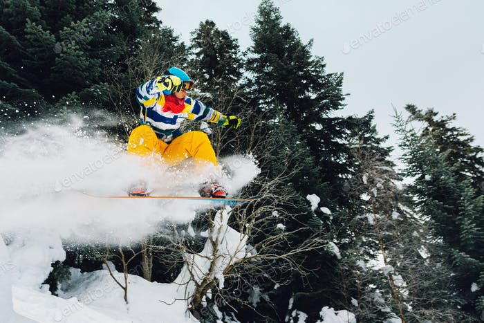 snowboarder is jumping and freeridingin the mountain forest