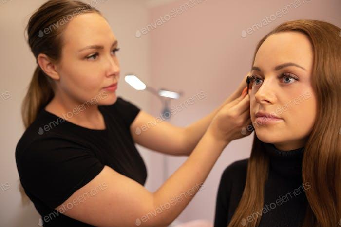 Weiblicher Spezialist, der Wimperntusche auf falschen Wimpern des Kunden verwendet