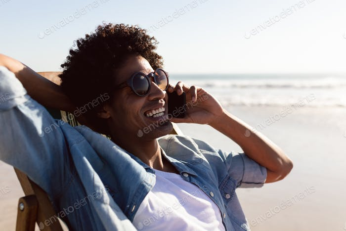 Happy African-american man talking on mobile phone while relaxing in a beach chair on the beach