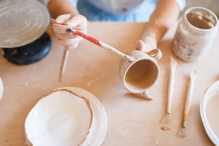 Female potter paints a pot, pottery workshop