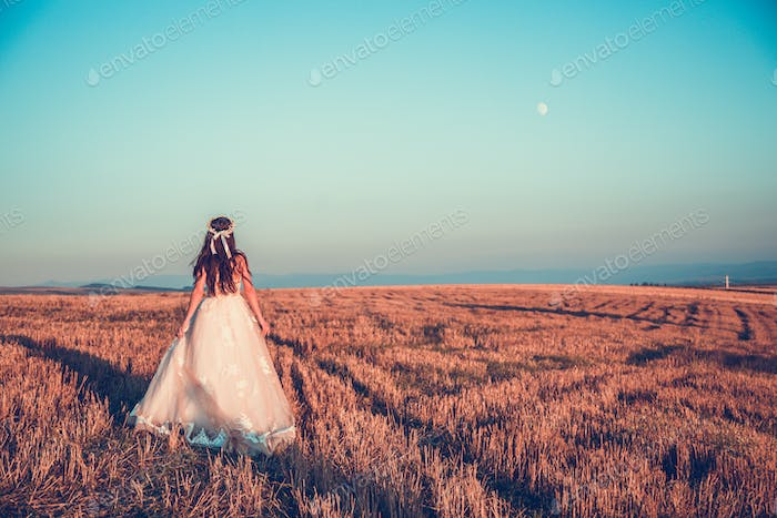 Bride in wedding dress goes on the road in a field at sunset