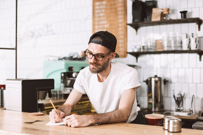 Thoughtful man in eyeglasses and cap writing in notepad working in cafe behind bar counter