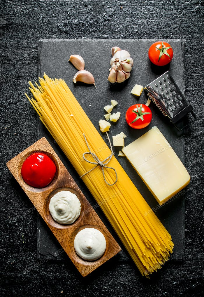 Raw spaghetti with Parmesan and different sauces.