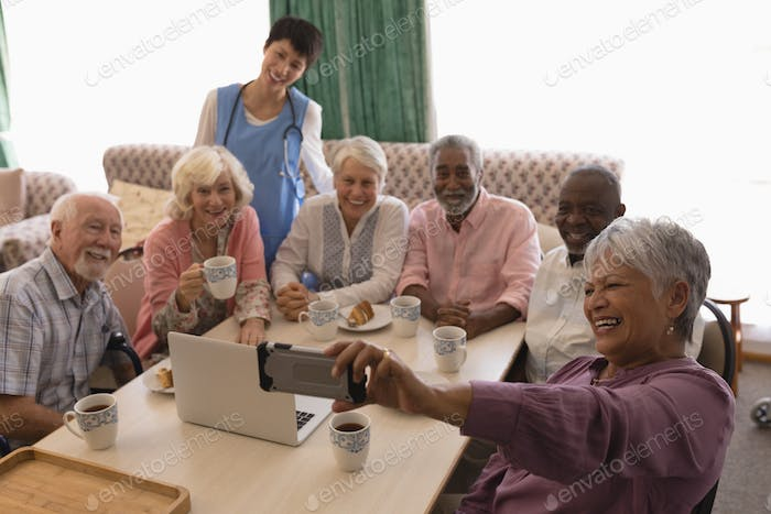 Senior woman taking selfie with mobile phone around a table at nursing home