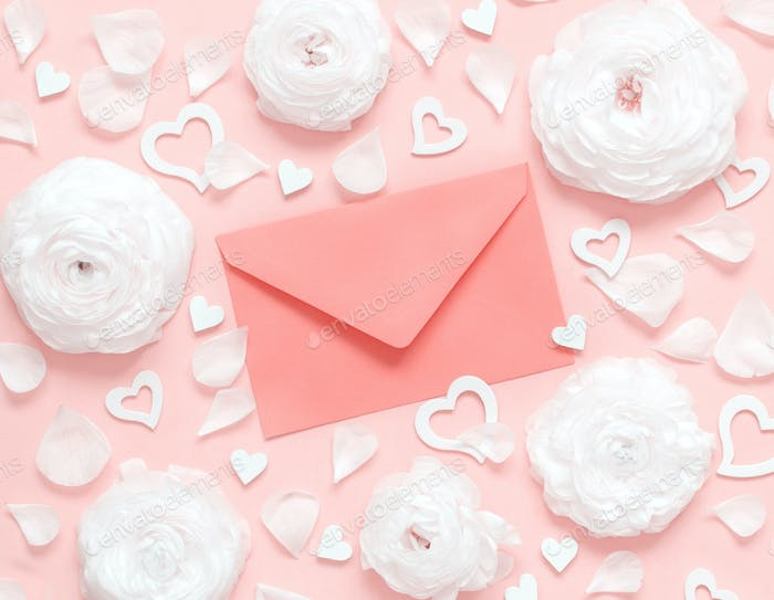 Pink envelope between cream flowers, petals and hearts on a light pink background