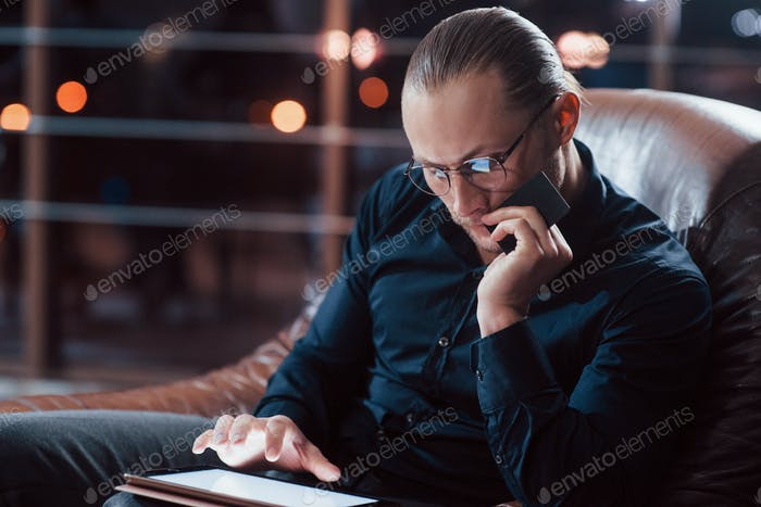 Stylish businessman in eyewear works alone in the office at nightime