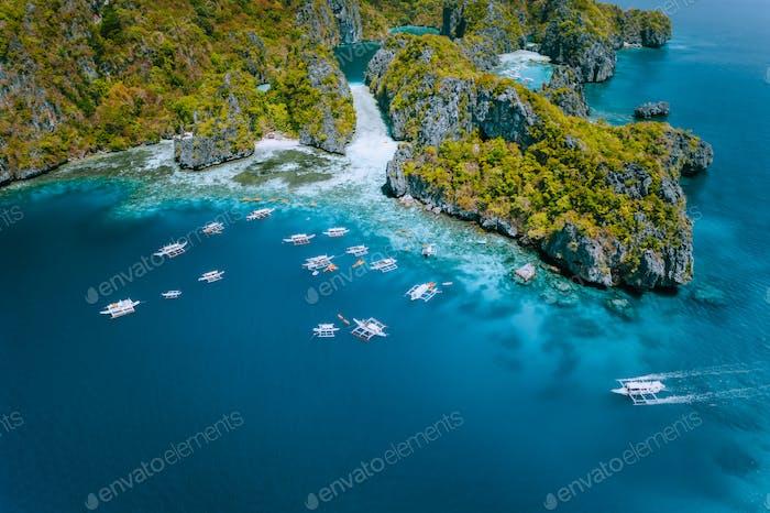 Aerial view of amazing Mililoc Island. Tourist boats near big Lagoon. El Nido, Palawan, Philippines
