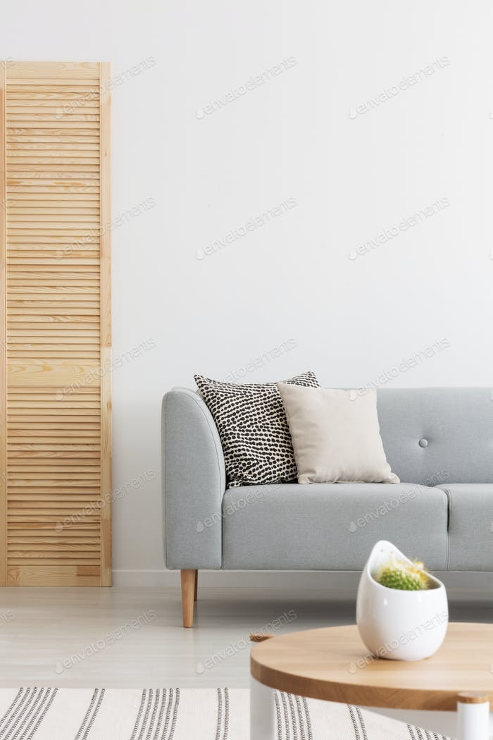 Wooden screen next to comfortable grey sofa with pillows in spac