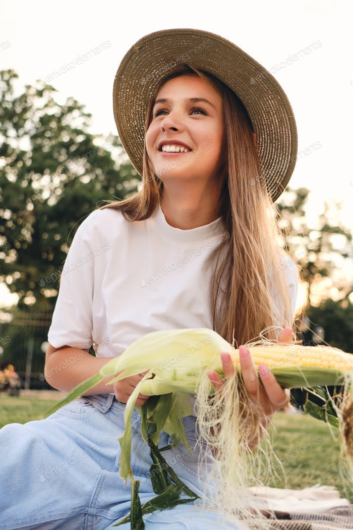 Beautiful smiling brown haired girl in straw hat joyfully cleaning corn on picnic in city park
