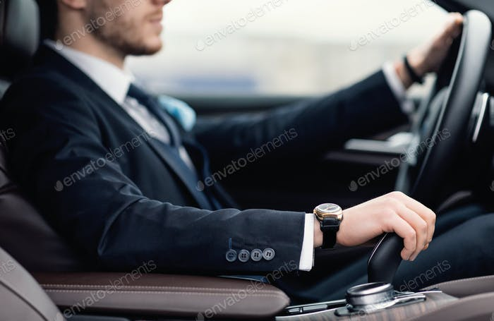 Confident man wearing suit and watch driving car