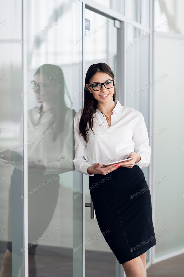 Business woman wearing white blouse standing in office hall with tablet computer and smiling