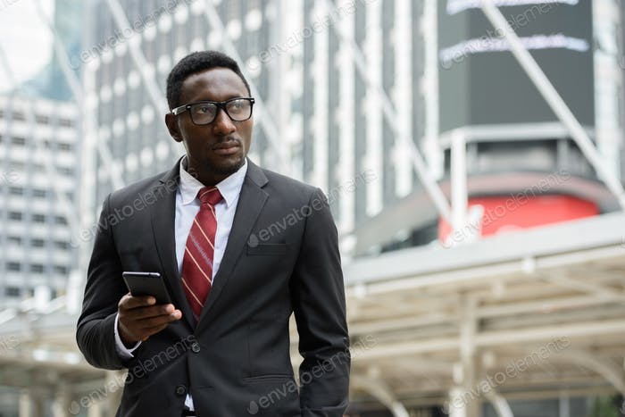 Young handsome African businessman holding mobile phone in front of modern building at Bangkok city