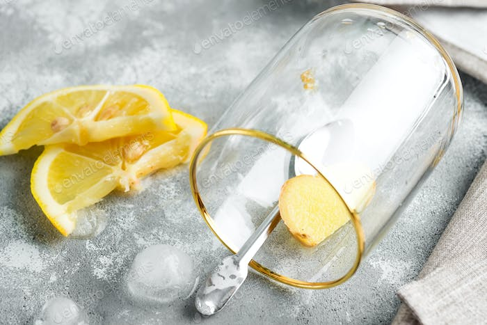 Refreshing homemade cold cocktail or lemonade from lemon in a glass with ice cubes on a marble grey