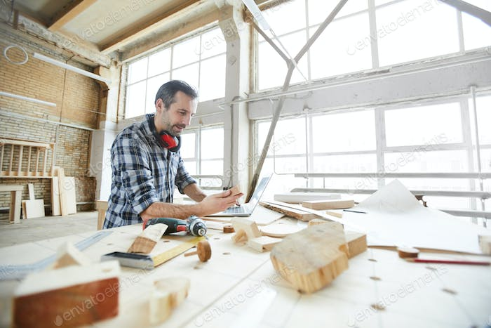 Carpenter searching for information on Internet while checking wooden details