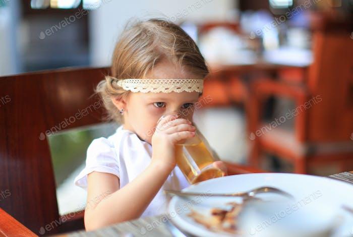 Liebenswert kleines Mädchen mit Frühstück im Restaurant