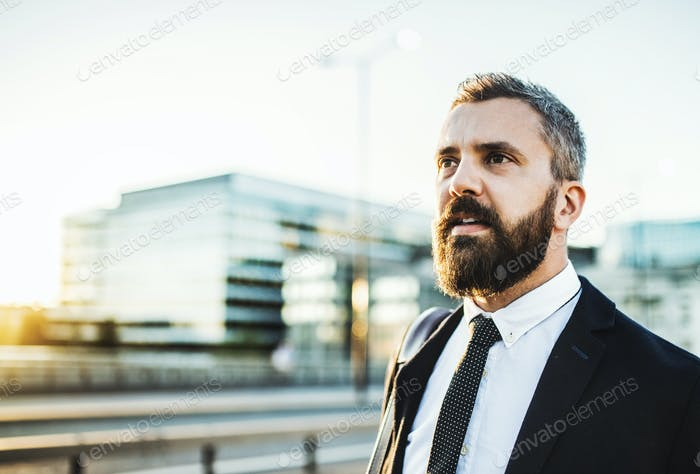 Hipster businessman walking on the street in the city. Copy space.