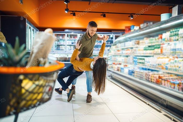 Amor casal de família dançando no supermercado