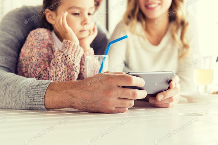 close up of family with smartphone at restaurant