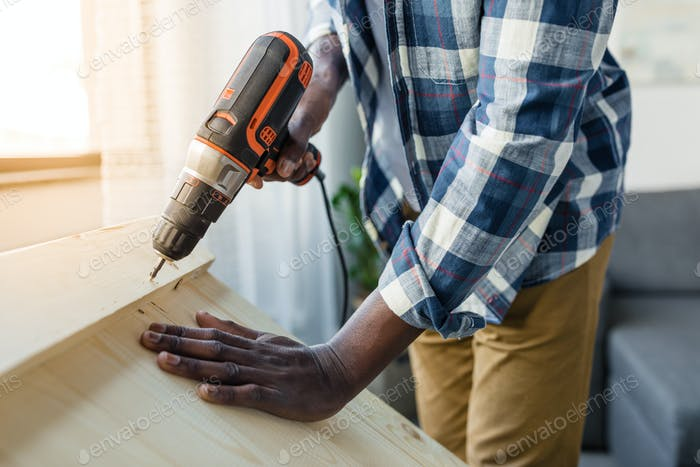 cropped shot of african-american man with perforator applying screw into wood