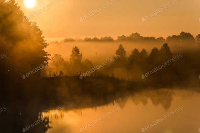 Sonnenaufgang über nebligen See im Herbst