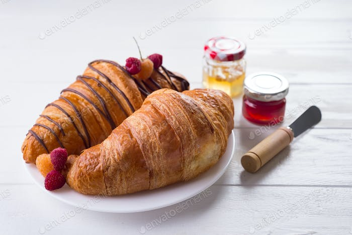 Fresh Croissant with berries and jam for breakfast isolated on white wooden background , copy space