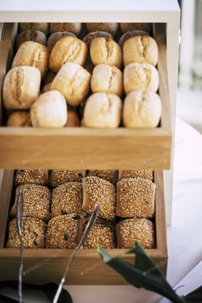 Bread buns in abundance on display at slatted shelf fixture in hotel or supermarket for sale