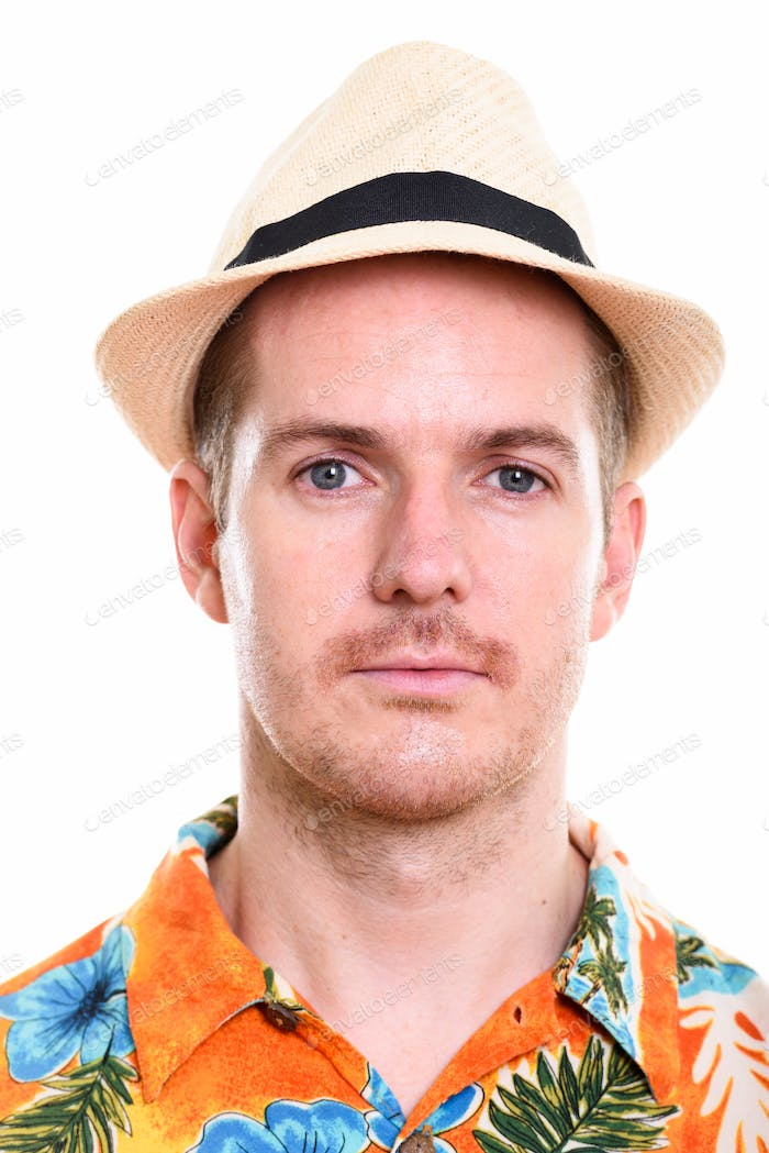 Face of man wearing Hawaiian shirt and hat ready for vacation