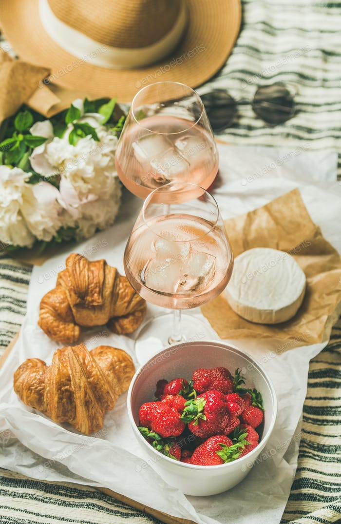 Flat-lay of rose wine, strawberries, croissants, brie cheese on board