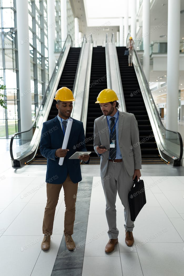 Young male architect discussing over digital tablet standing in office lobby