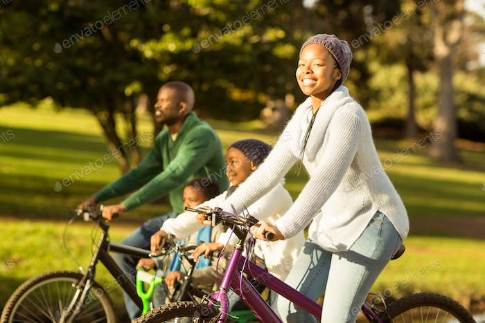 Side view of a young family doing a bike ride on an autumns day
