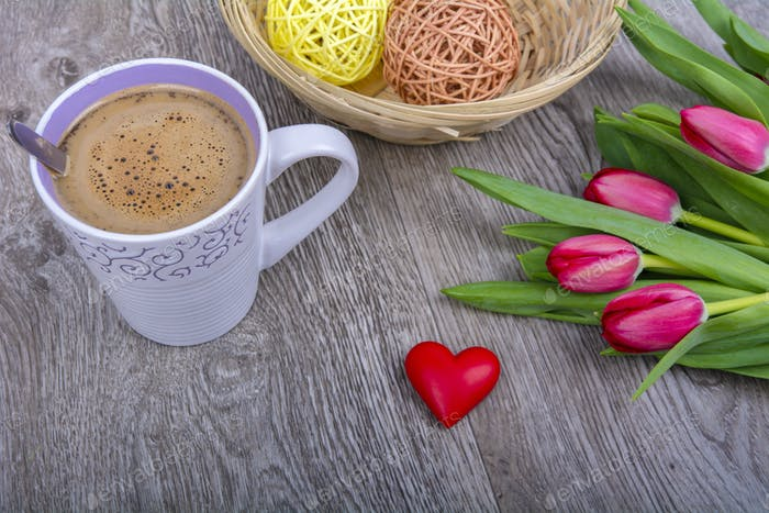 A cup of coffee and tulips on a wooden table