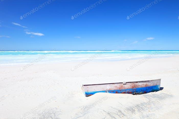 Altes Boot am weißen tropischen Sonnenstrand und einem blauen Himmel