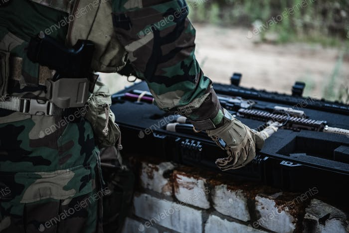 Military man preparing equipment of firearms to the mission. Pulls out assault rifle from the