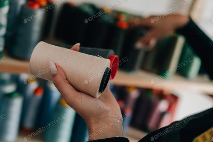 Tailor woman choosing colorful thread