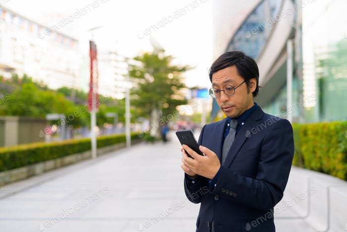Asian businessman using phone in the city outdoors