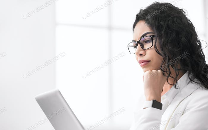 Serious mexican manager looking at her computer