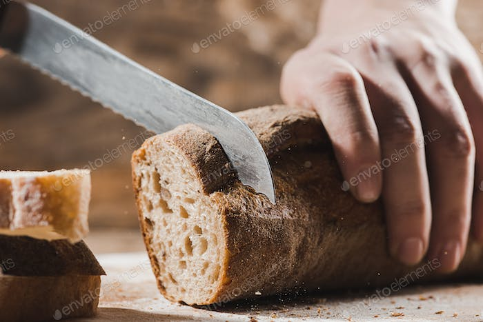 Whole grain bread put on kitchen wood plate with a chef holding gold knife for cut.